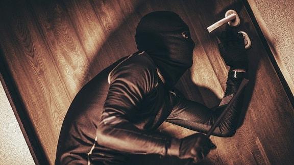 Einbrecher öffnet im Schutz der Dämmerung eine Wohnungstür.