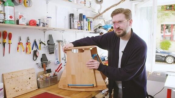 Ein junger Mann steht in seiner Werkstatt und erklärt seine Erfindung