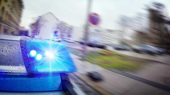Ein Polizeiauto rast mit Blaulicht durch eine Straße
