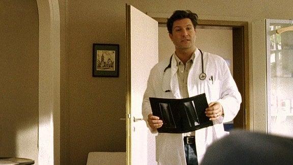 Dr. Kleist betritt sein Behandlungsimmer mit einem Röntgenbild