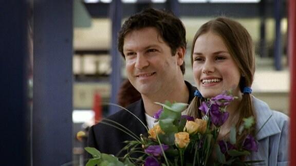 Dr. Kleist und seine Tochter holen jemand mit Blumen vom Bahnhof ab