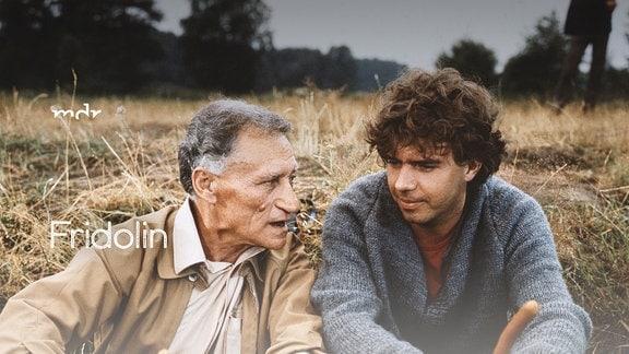 Fridolin sitzt mit einem älteren Mann am Lagerfeuer und grillt Würstchen.