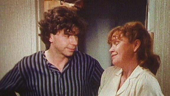 Ein junger Mann (Fridolin) steht neben einer Frau welche mit den Schultern zuckt und grinst