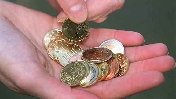 Münzen auf der Handfläche eines Mannes