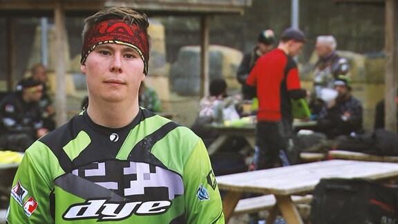 Ein junger Mann in Sportkleidung steht im Freiem. Im hintergund sind andere Sportler zu erkennen