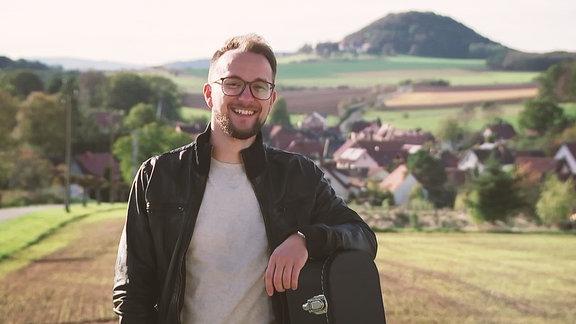 Ein junger Mann steht lächelnd im Freiem auf seinem Gitarrenkoffer aufgestützt. Im Hintergrund sind Hügel und ein kleines Dorf zu erkennen.