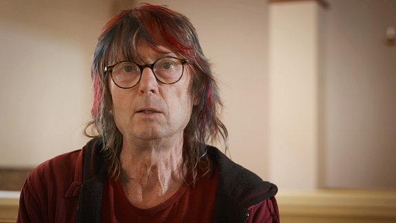 Portrait eines Mannes mit mit Brille und zotteligen Haaren – zum Teil in Rot und Blau gefärbt-