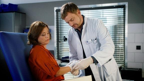 Ein Arzt behandelt eine Patientin im Behandlungsraum