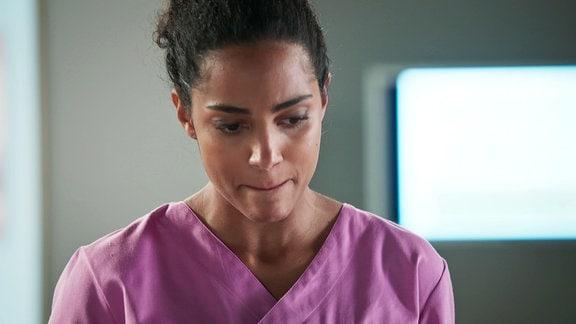 Eine Krankenschwester schaut zweifelnd zu Boden