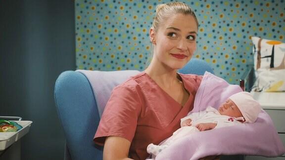 Eine Krankenschwester sitzt in einem Sessel und hält ein neugebohrenes Baby in den Armen