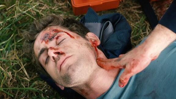 Ein Mann liegt blutverschmiert auf einer Wiese. Eine Hand fühlt, ob der Mann noch einen Puls hat.
