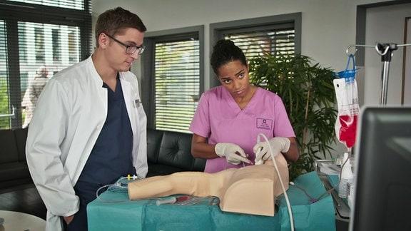 eine junge Auszubildende übt an einem Plastikkörper unter Aufsicht eines Doktors