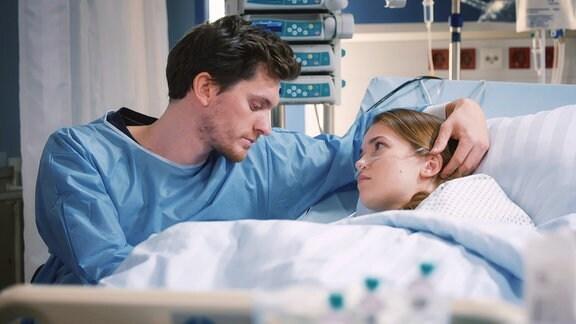 Ein junger Mann mit traurigem Blick, sitzt am Krankebett seiner Freundin und streichelt ihr über den Kopf