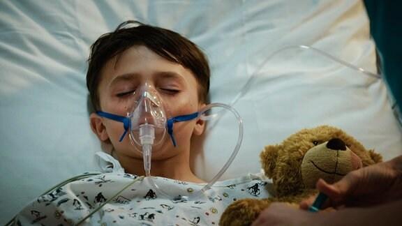 Ein kleiner junge liegt mit seinem Teddy im Krankenbett und muss künstlich beathmet werden