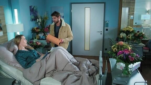 Ein Mann steht am Krankenhausbett einer Frau, es stehen viele Blumen im Zimmer.