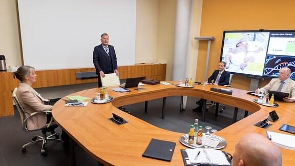 Dr. Roland Heilmann (Thomas Rühmann, mi.) versucht beim AVDGK - Allgemeiner Verband Deutscher Gesetzlicher Krankenkassen - eine Finanzierung für die zweite Behandlung seiner kleinen Patientin Feli Heller zu bekommen.