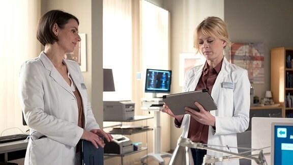 Dr. Maria Weber (Annett Renneberg, li.) fragt Dr. Ina Schulte (Isabell Gerschke, re.), ob sie nicht Lust auf einen Pärchenabend hätte.
