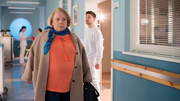 Pfleger Kris Haas (Jascha Rust) beobachtet, wie Esther Thaler (Martina Eitner-Acheampong) ziemlich aufgebracht die Klinik verlassen will.