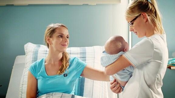 Eine junge frau im Krankenbett bekommt von einer Krankenschwester ihr neugebohrenes Baby gezeigt