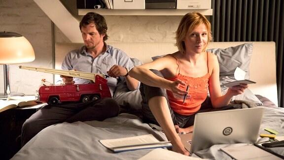 Ein junges Paar sitzt auf dem Bett. Der Mann spielt mit einem großen Feuerwehrauto und die Frau ist umgeben von Papierkram und einem Laptop