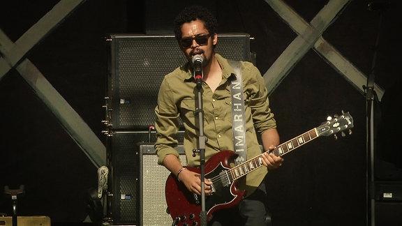 """Ein Sänger der Band """"Imarhan"""" Steht mit einer gitarre auf der Bühne und singt"""