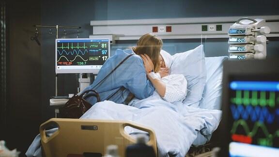 Eine Frau sthet am Krankenbett ihres Partners und küsst ihn