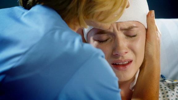 Eine junge Patientin mit Kopfverband liegt im Krankenbett und weint, während eine Krankenschwester sie tröstet