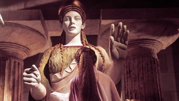 Eine Frau steht vor einer antiken Götter-Statue.
