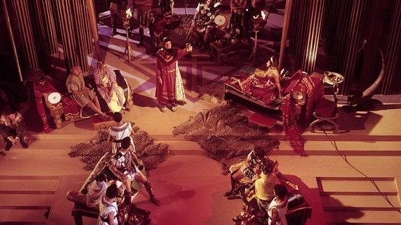 Mehrere Menschen sitzen in einem antiken Königshof beisammen.
