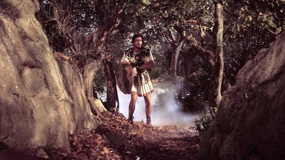Ein Mann mit Rüstung und Schwert zieht durch einen Wald.