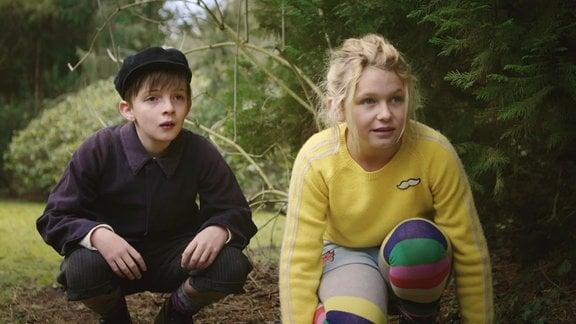 Ein Mädchen (Juna) und ein kleiner Junge verstecken sich an einem Baum