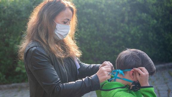 Leiterin einer Grundschule, bindet einem Schüler am Eingangstor der Schule einen Mundschutz an.