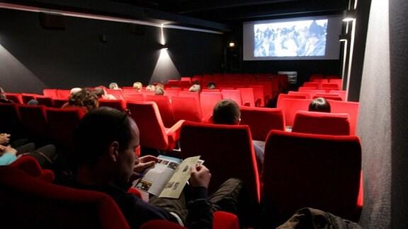 Menschen sitzen in einem noch erleuchteten Kinosaal