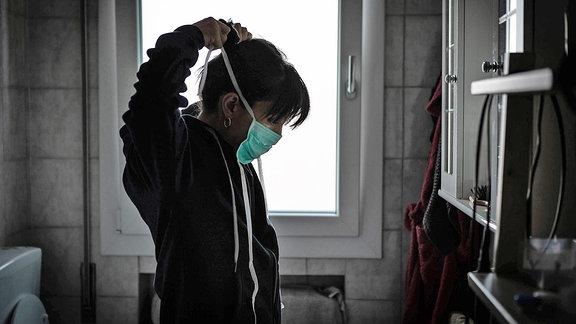 Eine junge Frau bindet sich einen Mundschutz um
