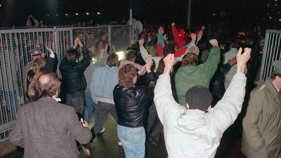 Jubelnde Menschen stürmen in der Nacht zum 10. November 1989 begeistert einen Grenzübergang.