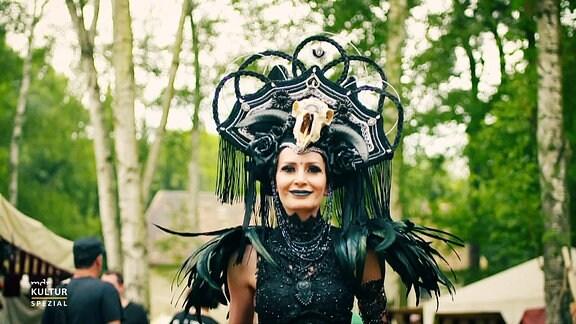 Eine junge Frau in einem schwarzen Kostüm läuft zum Wave Gothic Treffen durch einen Park