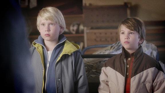 Zwei Jungs stehen vor einer erwachsenen Person
