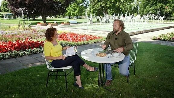 Eine Frau und ein Mann sitzen in einem Landschaftspark an einem schattigen Plätzchen und Trinken Kaffee