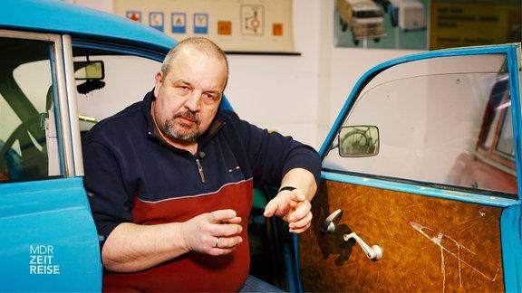 Ein Mann sitzt auf dem Beifahrersitzt eines alten Autos mit geöffneter Tür