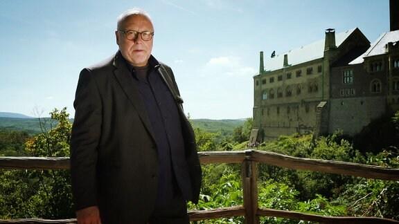 Ein älterer Herr steht an einem Aussichtspunkt. Im Hintergrund sinde Berge und eine Burg zusehen.