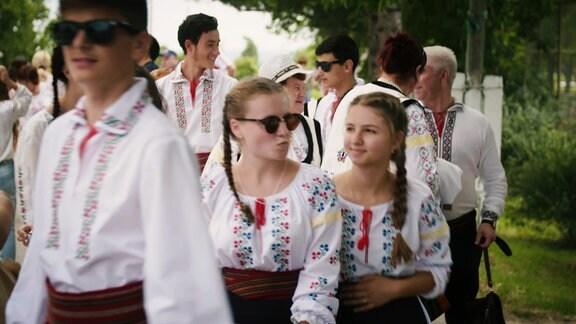 Eine Grruppe junger Menschen mit Sonnenbrillen und Smartphones, trägt Traditionelle Moldawische Kleidung