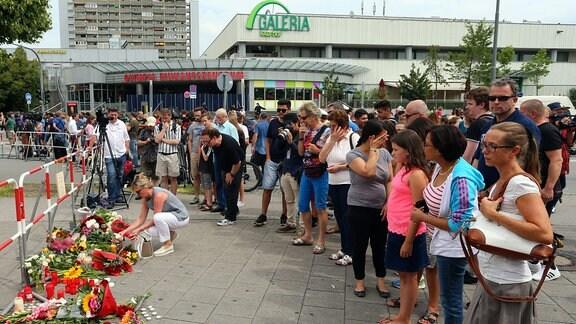 Passanten gedenken am 23.07.2016 nahe dem Olympia-Einkaufszentrum (OEZ) in München, einen Tag nach einer Schießerei mit Toten und Verletzten, den Opfern.