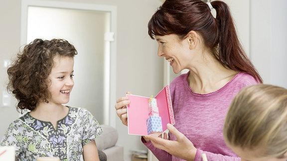 Kinder übereichen einer Frau ein Geschenk.