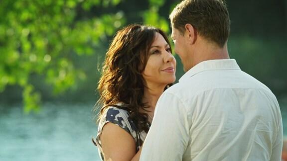 Eine Frau und ein Mann umarmen und schauen sich tief in die Agen
