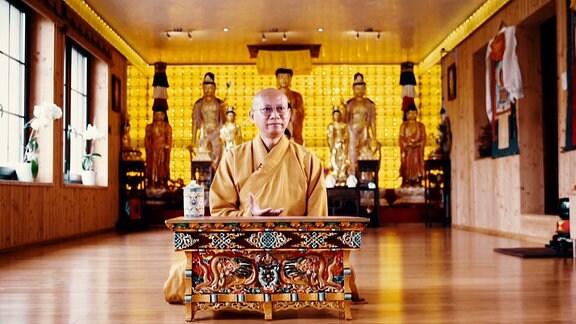 Ein buddistischer Mönch sitz in einem Raum im Schneidersitz und philosophiert
