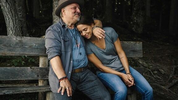 Sängerin Juli sitzt mit ihrem Vater Wim auf einer Bank am Waldrand. Er hat seinen Arm um sie gelegt und sich kuschelt ihren Kopf an seine Schulter
