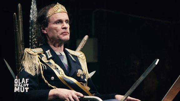 Olaf schubert sitzt in einem Tron und trägt ein Kostüm bestehend aus Diadem und einem königlichem Anzug