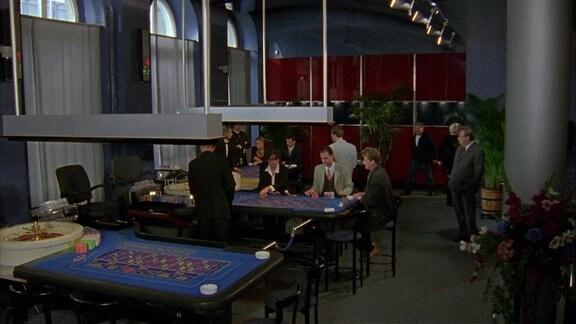 Menschen sitzen in einem Casion an Spieltischen.