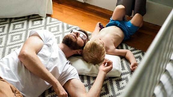 Ein Mann und ein Junge liegen auf dem Boden eines Kinderzimmers