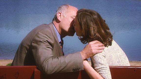 Ein älterer Herr und eine junge Frau küssen sich leidenschaftlich auf einer Bank am See